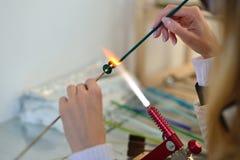 Le mani della donna con gli strumenti per la fusione di vetro, lampwork, fuoco Immagini Stock
