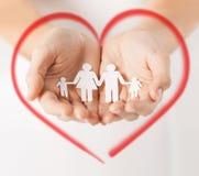 Le mani della donna con la famiglia di carta dell'uomo Immagini Stock