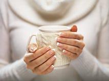 Le mani della donna con le unghie eleganti del manicure francese progettano la tenuta della tazza tricottata accogliente Concetto Immagine Stock