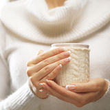 Le mani della donna con le unghie eleganti del manicure francese progettano la tenuta della tazza tricottata accogliente Concetto Fotografia Stock