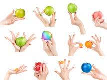 Le mani della donna con smalto differente ed i frutti messi hanno isolato w Immagini Stock