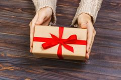 Le mani della donna danno il biglietto di S. Valentino avvolto o l'altro presente fatto a mano di festa in carta con il nastro ro Immagini Stock Libere da Diritti