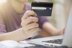 Le mani della donna del primo piano che tengono una carta di credito e che per mezzo del computer immagini stock libere da diritti