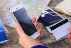 Le mani della donna del primo piano che tengono una carta di credito e che per mezzo del telefono cellulare Fotografia Stock