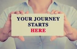 Le mani della donna di affari che tengono il segno della carta con il vostro viaggio inizia qui il messaggio Fotografia Stock