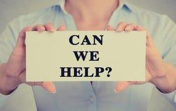 Le mani della donna di affari del primo piano che tengono il segno con possono noi testo di aiuto Fotografia Stock