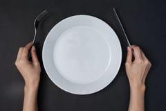 Le mani della donna due tengono un piatto bianco del coltello e del forcella e sulle sedere nere Immagine Stock
