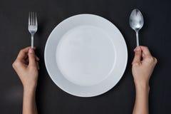 Le mani della donna due tengono un piatto bianco del cucchiaio e del forchetta e sulle sedere nere Fotografie Stock
