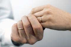 Le mani della donna e dell'uomo con le fedi nuziali Immagini Stock