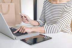 Le mani della donna facendo uso del registro della carta di credito e dello sho online di pagamenti Fotografia Stock