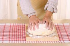 Le mani della donna impastano la pasta sulla tavola in cucina domestica Immagini Stock Libere da Diritti