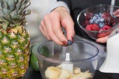 Le mani della donna mette i mirtilli in miscelatore per il frullato della frutta fotografie stock