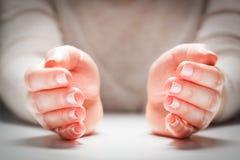 Le mani della donna nel gesto di protezione, cura Assicurazione di concetto, sicurezza Immagine Stock Libera da Diritti