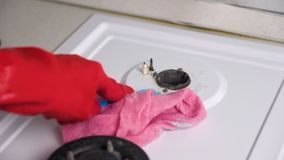 Le mani della donna nella stufa di gas sporca dei lavaggi di gomma rossi dei guanti con una spazzola e una spugna stock footage