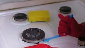 Le mani della donna nella stufa di gas sporca dei lavaggi di gomma rossi dei guanti con una spazzola e una spugna video d archivio