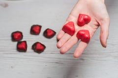 Le mani della donna in pieno dei dolci del cioccolato Fotografia Stock