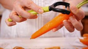 Le mani della donna sbucciano la carota fresca - fine su archivi video