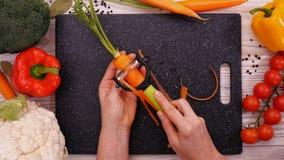 Le mani della donna sbucciano la carota fresca - movimento lento stock footage