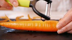 Le mani della donna sbucciano la carota fresca sul tagliere video d archivio