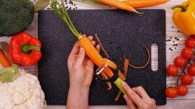 Le mani della donna sbucciano la carota sul tagliere - vista superiore video d archivio