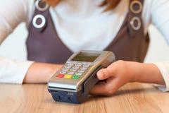 Le mani della donna si preparano al pagamento con la macchina del colpo della carta di credito Fotografia Stock