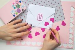 Le mani della donna sottoscrivono la carta della celebrazione del biglietto di S. Valentino Immagini Stock