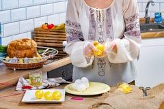 Le mani della donna stanno dipingendo le uova nel colore giallo sulla superficie di lavoro fotografia stock libera da diritti