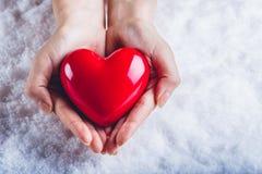 Le mani della donna stanno tenendo un bello cuore rosso lucido in un fondo della neve Amore e concetto del biglietto di S Immagine Stock Libera da Diritti