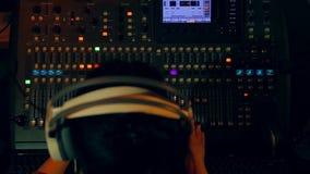 Le mani della donna sulle piste mescolantesi mescolantesi di una console per la discoteca a colori l'illuminazione stock footage