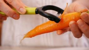 Le mani della donna tengono e sbucciano la carota fresca con le foglie verdi video d archivio
