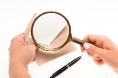 Le mani della femmina con la busta con la lente d'ingrandimento su fondo bianco fotografia stock libera da diritti