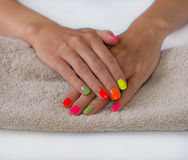 Le mani della giovane donna con il manicure luminoso Immagini Stock Libere da Diritti