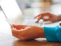 Le mani della giovane donna graziosa che tengono una carta di credito e che per mezzo del computer portatile per l'acquisto onlin Fotografia Stock Libera da Diritti