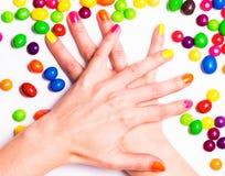 Le mani della giovane donna hanno attraversato con il manicure e le caramelle luminosi intorno Immagine Stock