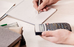 Le mani della persona che tiene il calcolatore e una matita Fotografia Stock