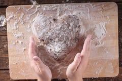 Le mani della ragazza che impastano pasta per il pan di zenzero immagini stock