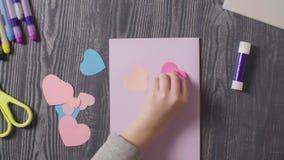 Le mani della ragazza che incollano una carta Giorno del `s del biglietto di S archivi video