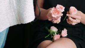 Le mani della ragazza con i fiori per la a capelli-fanno Acconciatura di cerimonia nuziale Primo piano video d archivio