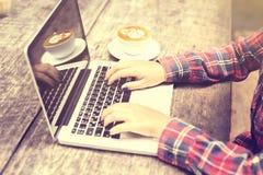 Le mani della ragazza con il computer portatile e la tazza da caffè su una tavola di legno Immagine Stock Libera da Diritti