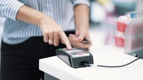 Le mani della ragazza fanno l'acquisto con il chip elettronico di uso della carta assegni, movimento lento stock footage
