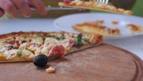 Le mani della ragazza hanno tagliato una fetta di pizza e la hanno messa su un piatto in caffè Colpo del carrello stock footage