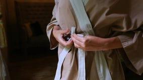 Le mani delle belle donne legano la cinghia sull'abito Comodità e intimity archivi video