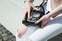 Le mani delle donne aprono una borsa di cuoio nera fotografia stock libera da diritti