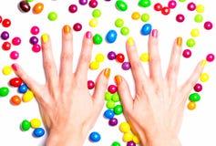 Le mani delle donne in caramelle luminose Immagine Stock