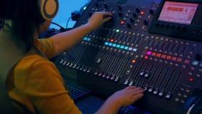 Le mani delle donne che funzionano alla console mescolantesi a colori l'illuminazione stock footage