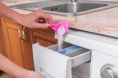 Le mani delle donne che mettono decolorante dentro alla lavatrice immagini stock libere da diritti