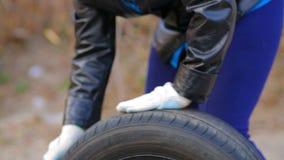 Le mani delle donne che rotolano sulla gomma di automobile dell'asfalto con il disco video d archivio