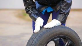 Le mani delle donne che rotolano sulla gomma di automobile dell'asfalto con il disco stock footage