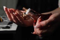 Le mani delle donne con le arti del chiodo sui chiodi che tengono bottiglia di profumo fotografia stock