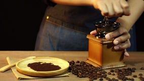Le mani delle donne del movimento lento stanno frantumando i chicchi di caffè stock footage